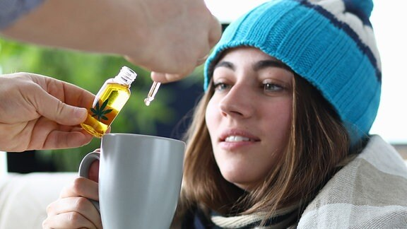 Eine rau mit Mütze hält eine Tasse, in die eine Flüssigkeit geträufelt wird
