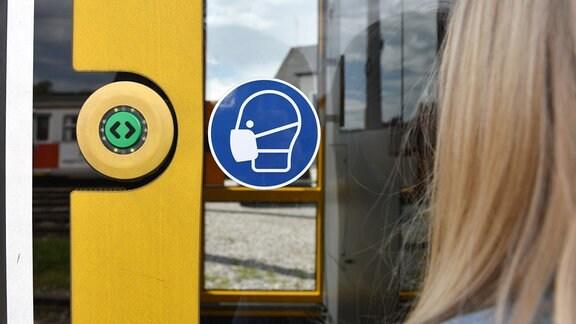 Ein Hinweis auf einer Straßenbahntür zum tragen einer Maske.