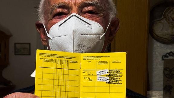 Mann hält Impfbuch