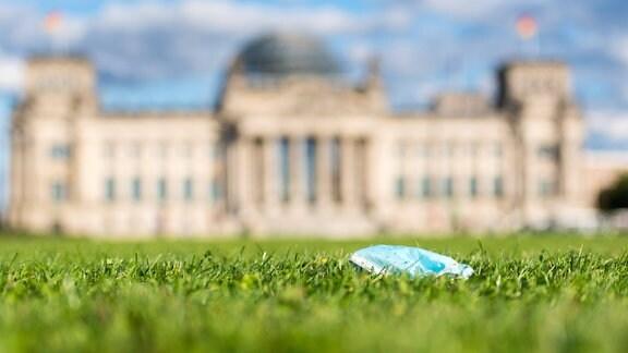 Im Bild ist eine Einwegmaske auf der Wiese vor dem Reichstagsgebäude zu sehen.