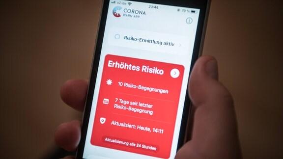 Ein Mobiltelefon mit geöffneter Corona Warn App und der Anzeige Erhöhtes Risiko
