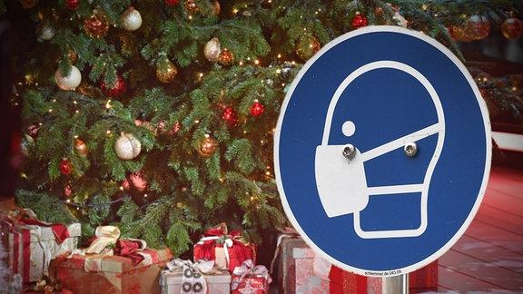 FOTOMONTAGE eines Maskenschildes vor einem Weihnachtsbaum