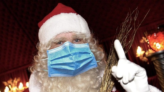 Ein Weihnachtsmann mit einer Gesichtsmaske