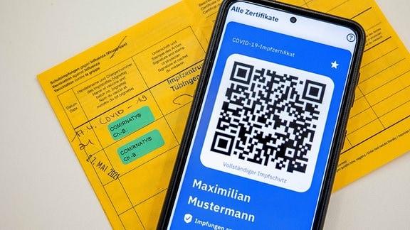 Gelber Impfpass neben CovPass-App
