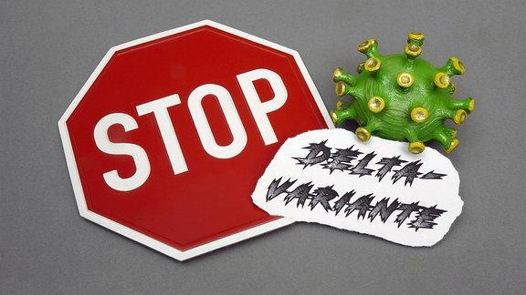 Neben einem Stopschild steht ein Corona-Modell mit dem Schriftzug Delta.