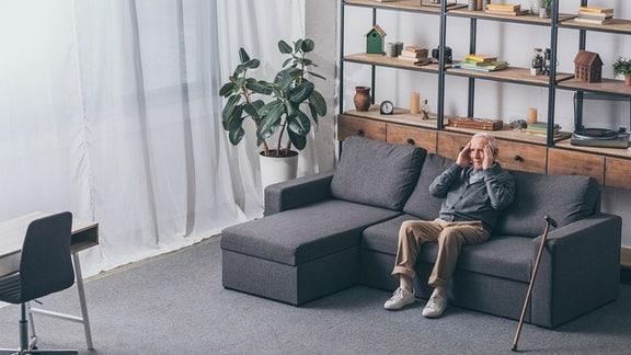 ein alter Mann sitzt auf dem Sofa