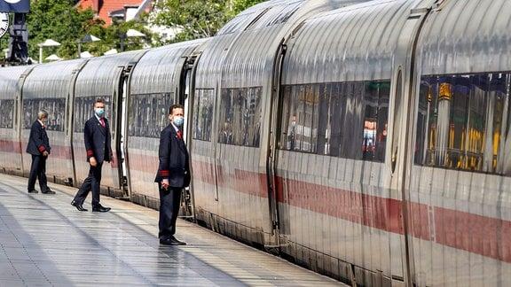 Zugbegleiter der Deutschen Bahn tragen Gesichtsmasken am Bahnsteig kurz vor der Abfahrt eines ICE Zugs