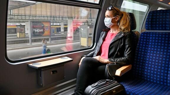 Frau mit Mundschutzmaske sitzt in Zug