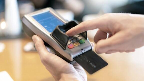 Eine Person benutzt ein Lesegerät für Kreditkarten.
