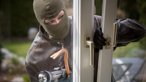 Ein Einbrecher bricht über das Fenster in ein Haus ein. (Symbolbild)