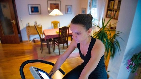 Eine Frau sitz im Wohnzimmer auf einem Ergometer
