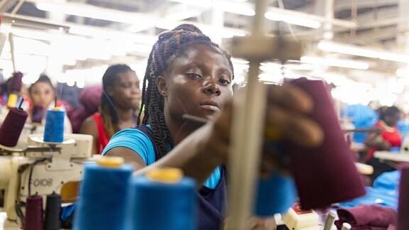 Junge Näherin in der Textilfabrik
