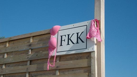 Schild mit der Aufschrift FKK, daneben hängt Unterwäsche