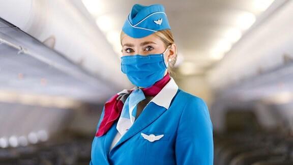 Stewardess von Eurowings mit Maske im Mittelgang eines Flugzeuges.