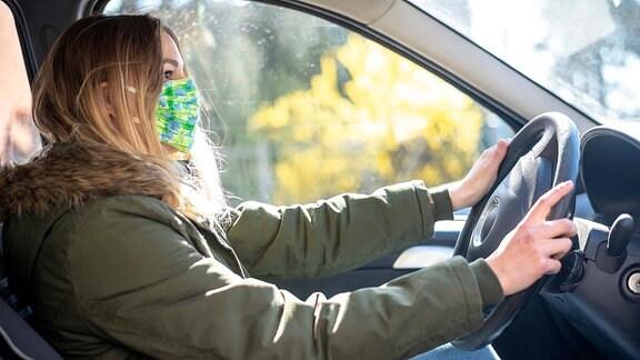 junge Frau mit Mundschutz im Auto