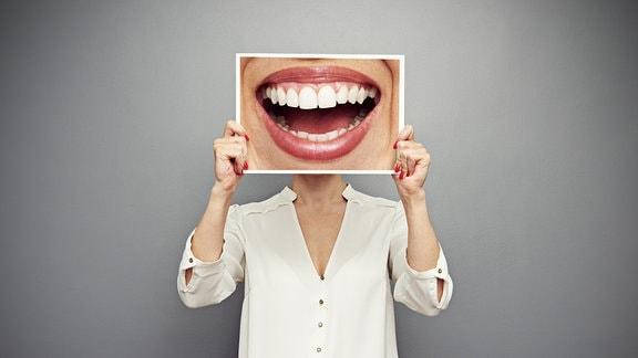 Frau hält sich Foto eines lachenden Mundes vor das Gesicht