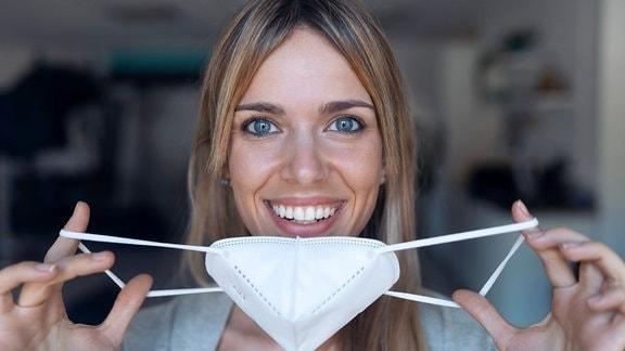 Lächelnde junge Frau hält einen Mundschutz.