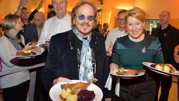 Ein Mann und eine Frau halten Teller mit angerichtetem Essen in die Kamera.