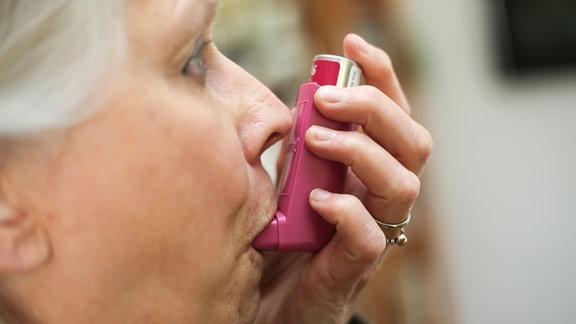 Eine Frau nimmt ein Asthmaspray zur Hand