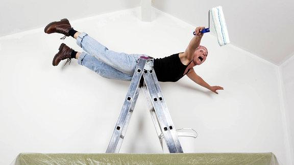 Eine Frau fällt schreiend von einer Malerleiter.