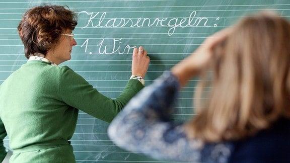 Lehrerin schreibt Klassenregeln an die Tafel