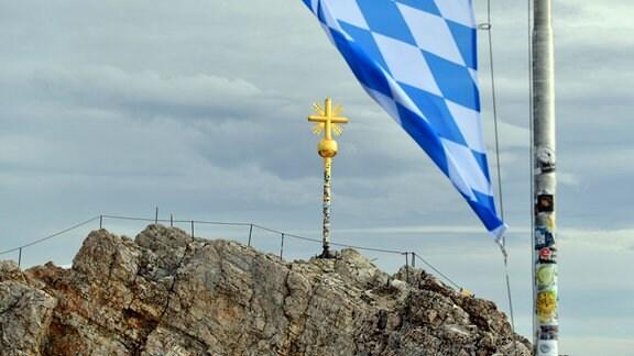 Die Bayerische Flagge mit blau weissen Rauten weht vor dem Gipfelkreuz der Zugspitze
