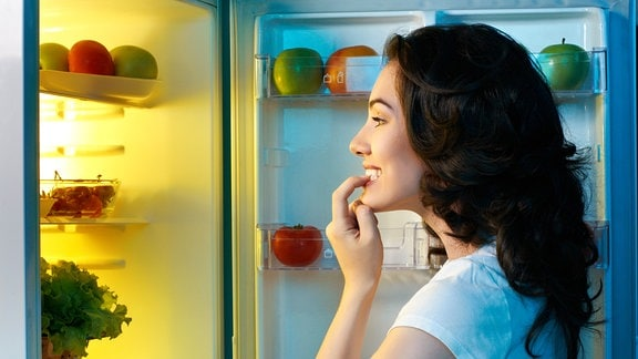Eine junge Frau sieht in einen Kühlschrrank