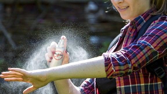 Junge Frau trägt vor einer Wanderung ein Insektenschutz-Spray auf die Haut auf.