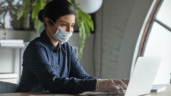 Eine junge Frau arbeitet mit Schutzmaske und Handschuhen an einem Laptop