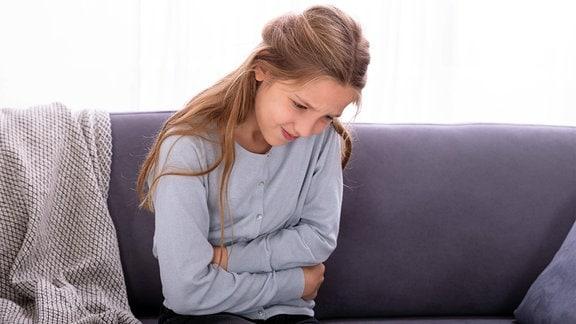 Mädchen mit Bauchschmerzen auf Sofa