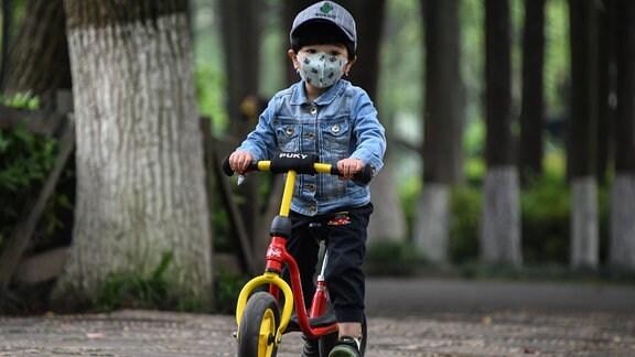 Ein Kind mit Mundschutz und Roller im Zoo von Wuhan