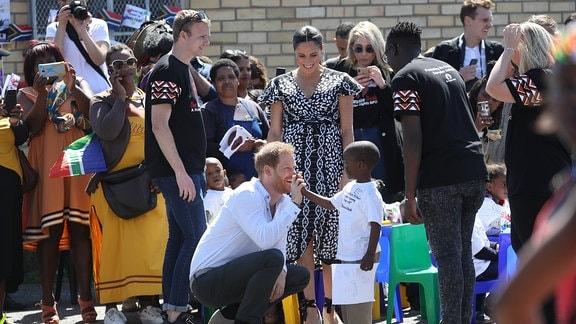 Harry gibt einem kleinen Jungen die Hand.