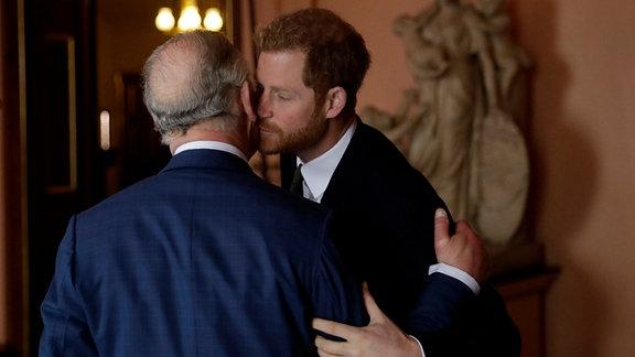 Der britische Prinz Harry (r) begrüߟt seinen Vater, Prinz Charles, mit einem Kuss auf die Wange.