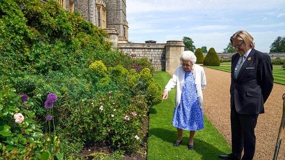 Königin Elisabeth II. betrachtet ein Beet in den Gärten von Schloss Windsor, wo sie eine Duke of Edinburgh-Rose erhielt, die ihr von Keith Weed, Präsident der Royal Horticultural Society, überreicht wurde (rechts).