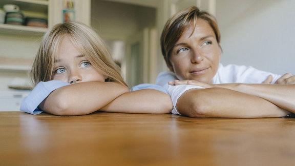 Mutter und Tochter lehnen sich auf einen Tisch.