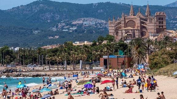 Viele Menschen an einem sommerlichen Strand in Mallorca.