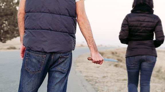 Symbolfoto - Ein Mann mit einem Messer in der Hand, steht hinter einer Frau.