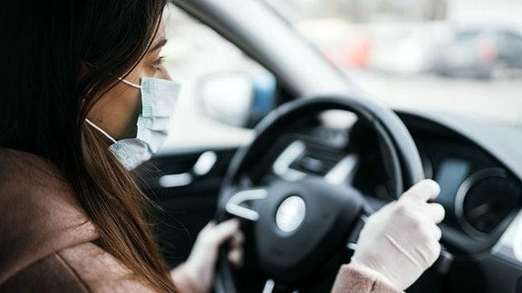 Frau mit langen dunklen Haaren sitzt mit medizinischer Maske und Einmalhandschuhen im Auto. Die Hände hat sie am Lenkrad.