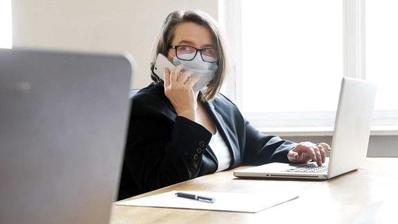 Frau im Büro am Arbeitsplatz mit Mundschutz um Ansteckung bei Kollegen zu vermeiden