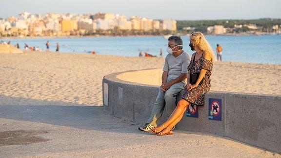Ein Mann und eine Frau mit Maske an einem Strand