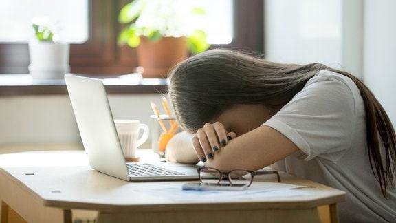 Eine Frau hat den Kopf auf den Armen liegend vor einem Laptop