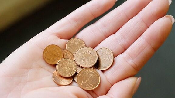 Eine Frau hält Ein- und Zwei-Cent-Münzen in ihrer Hand.