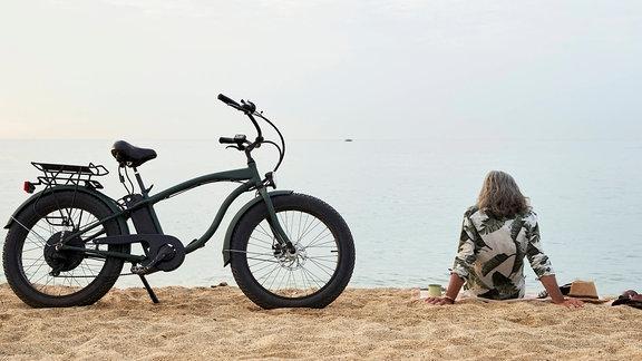ein Mann mit Fahrrad sitzt am Strand