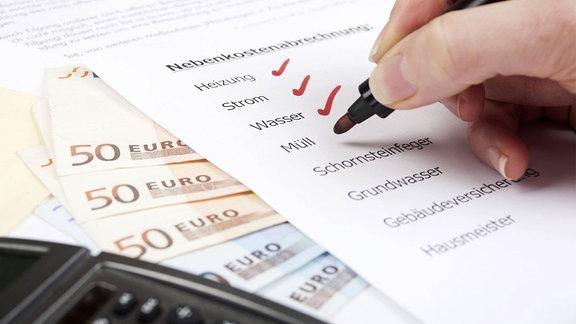 Nebenkostenabrechnung mit Geldscheinen und Taschenrechner.