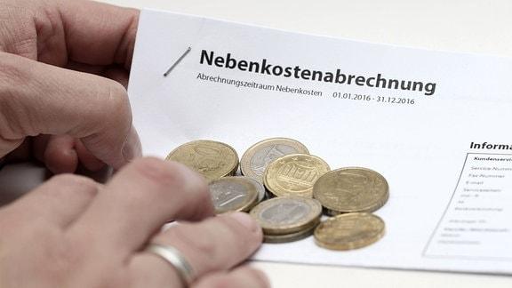 Hand hält Nebenkostenabrechnung mit Euro Münzen.