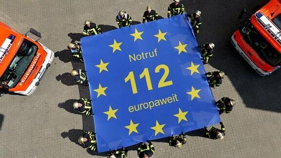 Feuerwehrmänner der Feuerwache 1 in Stuttgart halten am 19.07.2016 in Stuttgart (Baden-Württemberg) eine Fahne mit der Aufschrift «Notruf 112 europaweit». Am 29.07.2016 feiert der europaweite Notruf 112 sein 25-jähriges Bestehen.