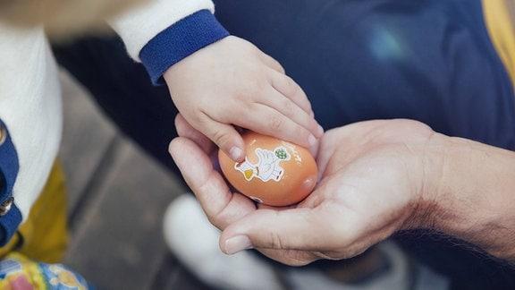 Zwei Hände halten ein buntes Osterei