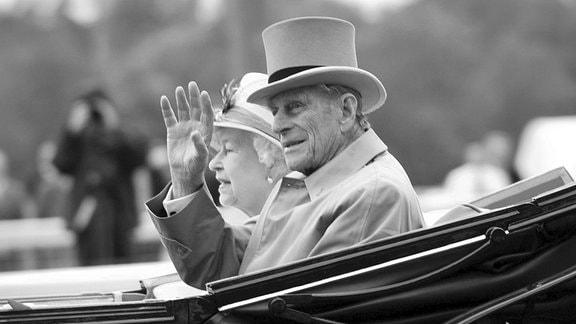 Prinz Philip und Queen Elizabeth winken aus einer Kutsche.
