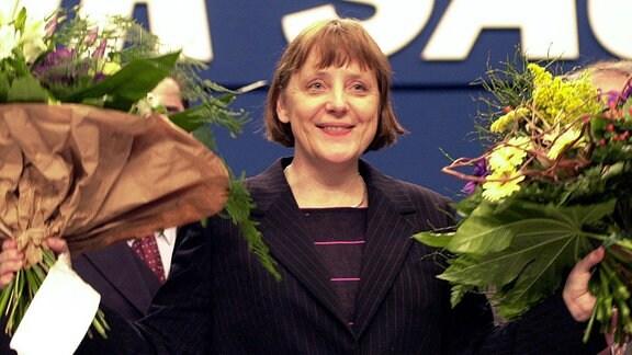 Nach ihrer Wahl zur neuen Vorsitzenden der CDU bedankt sich Angela Merkel bei den Delegierten des CDU-Bundesparteitages und winkt mit zwei Blumensträußen.