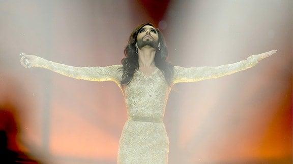 Conchita Wurst breitet die Arme aus und schaut nach oben.